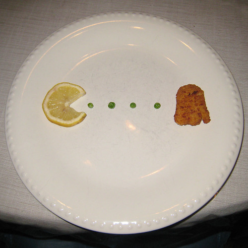 A lemon slice cut into the shape of Pac-Man pursues a line of peas and a ghost-shaped chicken nugget across a plate.